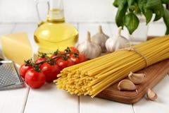 Ingredientes para la receta del bucatini: pastas, tomates, aceite, albahaca, ajo, queso en el fondo de madera blanco Fotografía de archivo libre de regalías