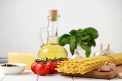 Ingredientes para la receta del plato italiano de las pastas en el fondo blanco Foto de archivo