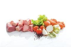 Ingredientes para la sopa del cerdo aislada por ejemplo porks, tomates, pimientas, cebollas, zanahorias en el piso de mármol blan fotos de archivo libres de regalías