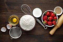Ingredientes para la torta o la empanada hecha en casa de la fresa con las bayas frescas en fondo rústico de madera Fotografía de archivo libre de regalías
