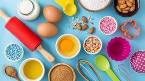 Ingredientes para la torta que cuece en la tabla azul Foto de archivo libre de regalías