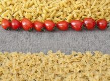 Ingredientes para las pastas con el tomate y el espacio vacío Foto de archivo