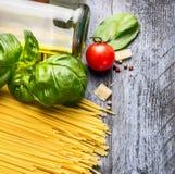 Ingredientes para los espaguetis con albahaca, el tomate, el aceite y el queso parmesano en la tabla de madera azul Imagenes de archivo