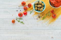 Ingredientes para los espaguetis de las pastas de la preparación - tomate, aceite de oliva, especias, hierbas, aceitunas verdes,  foto de archivo libre de regalías