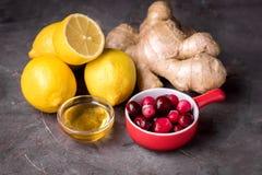 Ingredientes para los limones maduros Ginger Cranberry Dark Background de la bebida caliente sana Imagen de archivo libre de regalías