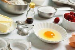 Ingredientes para los molletes o las magdalenas de la frambuesa que cuecen Fotografía de archivo libre de regalías