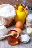Ingredientes para los pasteles de la miel en la tabla y el lino de madera oscuros viejos Imagenes de archivo