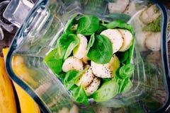 Ingredientes para los smoothies verdes del detox: espinaca, plátanos, semillas del chia imagen de archivo