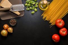 Ingredientes para a massa italiana Espaguetes, tomates, óleo, cebola, parmezan no fundo preto imagem de stock royalty free