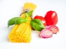 Ingredientes para o alimento italiano, massa no fundo branco imagens de stock