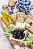 Ingredientes para o café da manhã mediterrâneo: pão fresco, queijo de feta, azeitonas e óleo extra virgem No fundo de madeira Foto de Stock