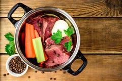 Ingredientes para o caldo da carne na bandeja na tabela de madeira: carne, cebola, cenoura, aipo, salsa e especiarias Fotografia de Stock Royalty Free