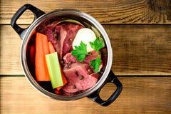 Ingredientes para o caldo da carne na bandeja na tabela de madeira: carne, cebola, cenoura, aipo, salsa e especiarias Foto de Stock