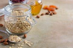 Ingredientes para o granola caseiro da farinha de aveia Os flocos da aveia, mel, porcas da amêndoa, secaram arandos e abricós Con Foto de Stock