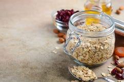 Ingredientes para o granola caseiro da farinha de aveia Os flocos da aveia, mel, porcas da amêndoa, secaram arandos e abricós Con Imagem de Stock