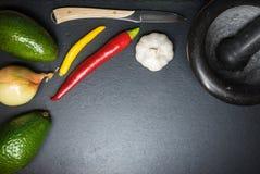 Ingredientes para o guacamole na tabela escura da ardósia com almofariz e faca imagem de stock royalty free