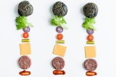 Ingredientes para o hamburguer preto sobre o fundo branco foto de stock royalty free