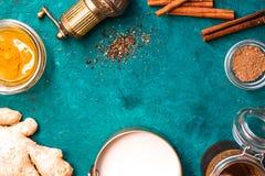 Ingredientes para o latte da cúrcuma no fundo ciano horizontal imagem de stock