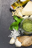 Ingredientes para o pesto: pinhões, manjericão, Parmesão, azeite extra virgem, alho e sal Sobre a pedra preta Fotografia de Stock Royalty Free