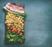 Ingredientes para o prato do gnocchi da batata com espinafres, tomates e bacon Fotografia de Stock
