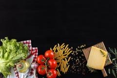 Ingredientes para o prato italiano Queijo parmesão, massa e legumes frescos Em um fundo de madeira preto velho fotos de stock royalty free