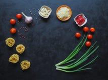Ingredientes para os espaguetes em um fundo preto copie o espaço para seu texto Fotografia de Stock