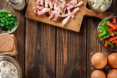Ingredientes para preparar a omeleta com bacon e vegetais imagem de stock