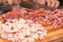 Ingredientes para preparar uma placa do alimento Bacon e salsicha italiana que estão sendo cortados Foto de Stock Royalty Free