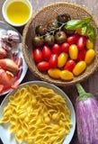 Ingredientes para a salada de massa tomates coloridos, cebola, alho, e foto de stock