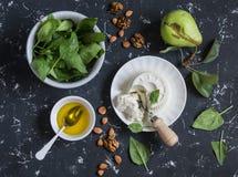 Ingredientes para a salada - espinafre fresco, goat& macio x27; queijo de s, pera, mel, porcas Em um fundo escuro Imagem de Stock