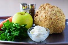 Ingredientes para a salada fresca com aipo, maçã, cenoura com iogurte em uma placa de metal em um fundo cinzento Comer saudável Fotos de Stock