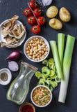 Ingredientes para a sopa da desintoxicação - caldo na garrafa, aipo, grãos-de-bico, alho-porros, tomates, cebolas vermelhas, espe Fotos de Stock Royalty Free