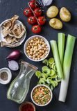 Ingredientes para a sopa da desintoxicação - caldo na garrafa, aipo, grãos-de-bico, alho-porros, tomates, cebolas vermelhas, espe Fotografia de Stock Royalty Free