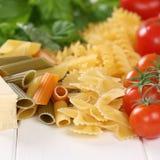 Ingredientes para uma refeição com tomates, che dos macarronetes da massa do Parmesão Fotos de Stock