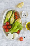 Ingredientes para uma salada fresca com os tomates do abacate e de cereja imagens de stock royalty free