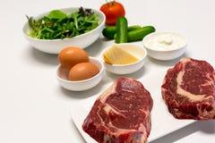 Ingredientes para una cena del filete y de la ensalada imagen de archivo