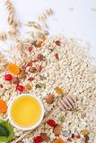 Ingredientes para una harina de avena sana del desayuno, miel, nueces, bayas, frutas, fotografía de archivo