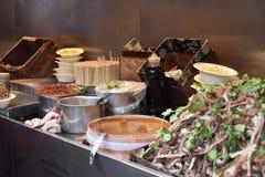 Ingredientes para una sopa china con la carne de cerdo en un mercado chino local en Pekín fotos de archivo