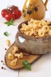 Ingredientes: pastas en un pote de cerámica, tomates y jarra Foto de archivo libre de regalías