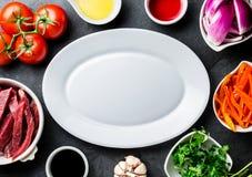 Ingredientes pour faire cuire le saltado péruvien de Lomo de plat - boeuf de filet, légumes autour du plat blanc Vue de doigt Images stock