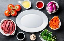 Ingredientes pour faire cuire le saltado péruvien de Lomo de plat - boeuf de filet, légumes autour du plat blanc Vue de doigt Photos libres de droits