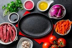Ingredientes pour faire cuire le saltado péruvien de Lomo de plat - boeuf de filet, légumes autour de plat noir Vue de doigt Image stock