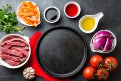 Ingredientes pour faire cuire le saltado péruvien de Lomo de plat - boeuf de filet, légumes autour de plat noir Vue de doigt Photo stock