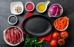 Ingredientes pour faire cuire le saltado péruvien de Lomo de plat - boeuf de filet, légumes autour de plat noir Vue de doigt Photos libres de droits