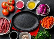 Ingredientes pour faire cuire le saltado péruvien de Lomo de plat - boeuf de filet, légumes autour de plat noir Vue de doigt Photographie stock