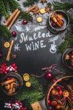 Ingredientes reflexionados sobre tradicionales del vino con cocinar el pote, las tazas y las ramas del abeto en fondo negro de la Imagen de archivo
