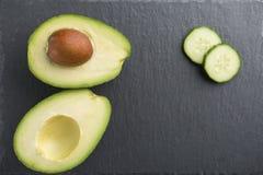 Ingredientes verdes do batido - abacate, pepino em um fundo escuro Fotografia de Stock Royalty Free