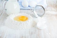 Ingredientes y herramientas para cocer - harina, huevos y vidrio de leche en el fondo rústico de madera de la tabla, foco selecti Foto de archivo