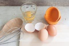 Ingredientes y herramientas para hacer una torta, huevos, tazas de la panadería Foto de archivo