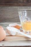 Ingredientes y herramientas para hacer una torta, huevos, tazas de la panadería Fotografía de archivo libre de regalías
